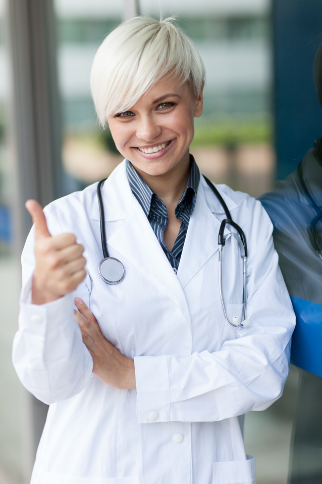 smiling attractive female doctor in front of a glass wall